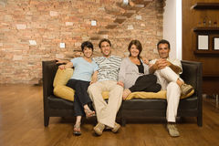 Herangewachsene Familie auf dem Sofa Lizenzfreie Stockbilder