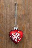 Herat shaped Christmas ornament. Red heart shaped Christmas ornament hanging by a rusty nail on an old wooden door stock photo