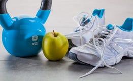 Herauf Übungskonzept mit Turnschuhen, Kesselglocke und Apfel tonen Stockbild