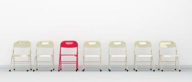 Ein roter Stuhl, der heraus in Folge von den Stühlen steht Lizenzfreies Stockfoto
