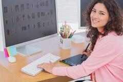 Herausgeber unter Verwendung der Grafiktablette, zum der Arbeit und des Lächelns an der Kamera zu tun Lizenzfreie Stockfotografie