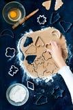 Herausschneiden der Weihnachtssymbole im Teig Stockfotografie