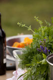 Herb Bouquet. Close up of herb bouquet in the foreground; a bottle of wine and salad bowl with the chopped carrots in the background. Shallow depth of field royalty free stock photography