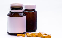 Herb capsule spilling out of pill a bottle. With closed bottle on white background Stock Photos