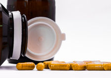 Herb capsule spilling out of pill a bottle Stock Photography
