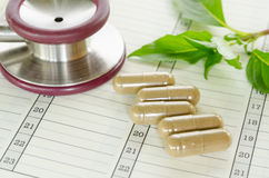 Herb capsules spilling out of a bottle on calendar background. Stock Image