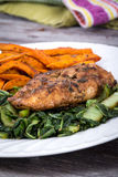 Herb chicken breast meal. With greens and sweet potato fries on rustic table stock photo