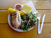 Herb chicken plate with nalo greens salad, corn on the cob, and Royalty Free Stock Photo