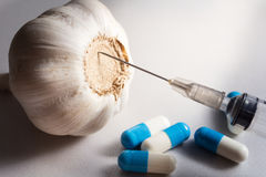 Herb for health, Garlic with capsules and syringe. Royalty Free Stock Image