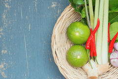 Herb ingredient of Tom Yum spicy soup. Herb ingredient of Tom Yum spicy soup in wicker basket. Traditional Thai food on blue plywood background. image top view Stock Images