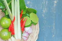 Herb ingredient of Tom Yum spicy soup. Herb ingredient of Tom Yum spicy soup in wicker basket. Traditional Thai food on blue plywood background. image top view Stock Image