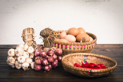 Herb ingredients,  onion, garlic and eggs on dark wood table Royalty Free Stock Photo