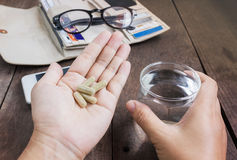 Herb medicine on hand and glass of water on work table Stock Images