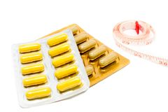 Herb pills blister pack and measuring tape for diet concept.  Royalty Free Stock Photo