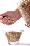 Herb preparation. Measuring prepared dried herbs into a container Royalty Free Stock Image