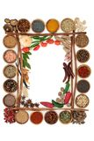 Herb and Spice Border. Herb and spice background with inner border of cinnamon sticks on white with copy space stock photo