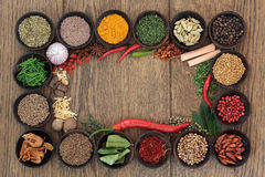 Herb and Spice Border. Herb and spice selection forming an abstract background border over oak stock photos