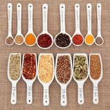 Herb and Spice Measurement. Herb and spice selection in metric measuring spoons and scoops over hessian Royalty Free Stock Photo