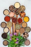 Herb and Spice Seasoning. Herb and spice fresh and dried food seasoning loose and in wooden bowls and olive wood spoons on rustic wood background. Top view stock image