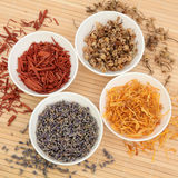 Herb and Spice Selection. Lavender, marigold and chamomile flowers with sandalwood spice in white porcelain bowls over bamboo background Royalty Free Stock Photos