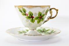 Herbaciana filiżanka i spodeczek z Bożenarodzeniowym holly drukującym Fotografia Royalty Free