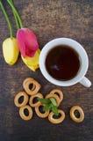 Herbaciana filiżanka, tulipanowy kwiat na drewnianym tle, Obrazy Royalty Free