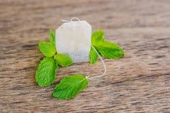 Herbaciane torby na drewnianym tle z świeżym melissa, mennica Herbata z zdjęcie stock