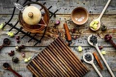 Herbacianego przyjęcia set Herbaciany garnek, filiżanki, wysuszeni herbaciani liście, fllowers, pikantność na drewnianego tła odg Obraz Stock