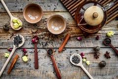 Herbacianego przyjęcia set Herbaciany garnek, filiżanki, wysuszeni herbaciani liście, fllowers, pikantność na drewnianego tła odg Zdjęcia Royalty Free