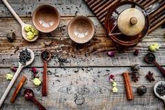 Herbacianego przyjęcia set Herbaciany garnek, filiżanki, wysuszeni herbaciani liście, fllowers, pikantność na drewnianym tło odgó Obraz Royalty Free