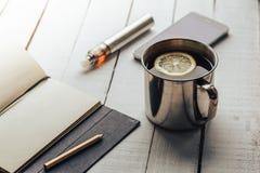 Herbacianej filiżanki, telefonu komórkowego, notatnika, ołówkowego i elektronicznego papieros dla vaping, Zdjęcie Stock