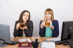 Herbacianej przerwy dwa biurowi pracownicy przy biurkiem Obraz Royalty Free