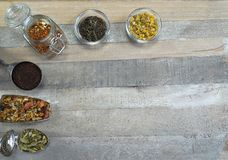 Herbaciany asortyment przy łyżkami w szkle przy przy drewnianym tłem i fotografia stock