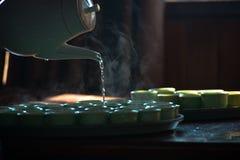 Herbaciany czas, dolewanie, czajnik, filiżanki Obrazy Royalty Free
