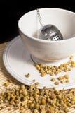Herbaciany durszlak z suchym chamomile w białej filiżance obrazy stock