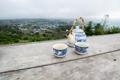 Herbaciany garnek z filiżanką ustawiającą na drewnianym stole przed widokiem górskim Zdjęcia Stock