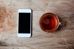 herbaciany i biały telefon komórkowy na starym drewnianym stole Zdjęcie Royalty Free