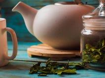 Herbaciany pojęcie, filiżanka z teapot dekorował z zieloną liść herbatą zdjęcia royalty free