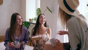 Herbaciany przyjęcie, rozochocone dziewczyny w seksownych bathrobes opowiada z filiżankami i pudełkiem cukierki w domu zbiory
