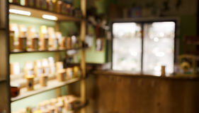 Herbaciany wnętrze zamazujący sklep z kawą abstrakcjonistyczny tło, półki z próbkami, plecy światło i bar iluminujący, pokazujemy Zdjęcie Stock