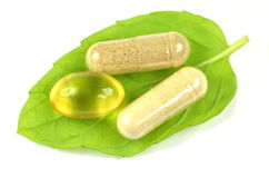 Herbal capsules and fish oil capsule on mint leaf Royalty Free Stock Image