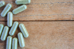 Herbal capsules on wood Stock Photo