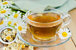 Herbal chamomile tea in cup with strainer on board Royalty Free Stock Photo