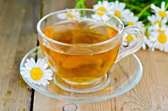 Herbal chamomile tea in a glass cup on a board Royalty Free Stock Photos
