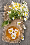 Herbal chamomile tea in glass cup on wooden table Royalty Free Stock Photography