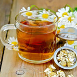 Herbal chamomile tea in a mug with strainer on the board Royalty Free Stock Image
