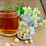 Herbal chamomile tea in mug with strainer on board Stock Images