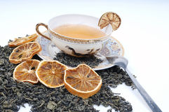 Herbal cup of tea with leaves and lemons. Tea pot with cup and leaves of mint Stock Images