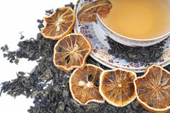 Herbal cup of tea with leaves and lemons. Tea pot with cup and leaves of mint royalty free stock image