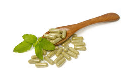 Herbal drug capsules inwooden spoon Royalty Free Stock Photo